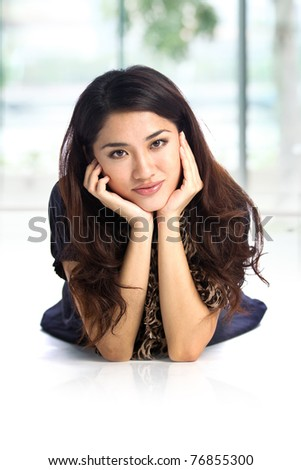 Portrait of pretty young Chinese woman lying on the floor with hand on chin and smiling. Beautiful Chinese woman with a friendly smile at home. - stock photo