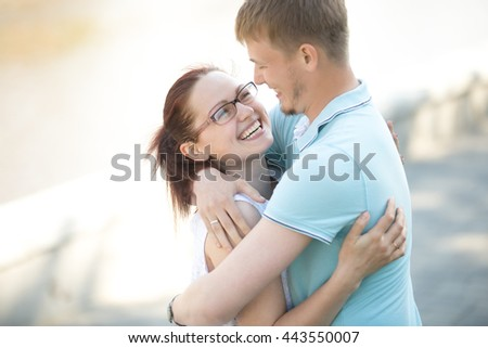 Portrait of pretty young dark-haired woman standing in her husband arms laughing outside. They are walking in the park on a nice sunny summer day. Outdoors image - stock photo