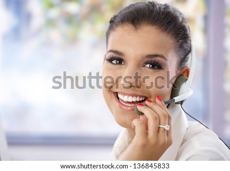 Portrait of pretty young dispatcher, smiling, looking at camera. - stock photo