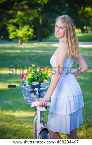 Portrait of pretty young female standing next to bicycle with flowers basket in the park. Outdoor and lifestyle concepts.  - stock photo