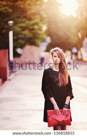 Portrait of pretty young female with a red bag in hands - stock photo