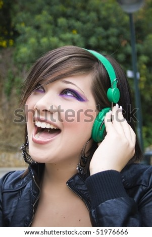 portrait of pretty young girl listening music with enthusiasm - stock photo
