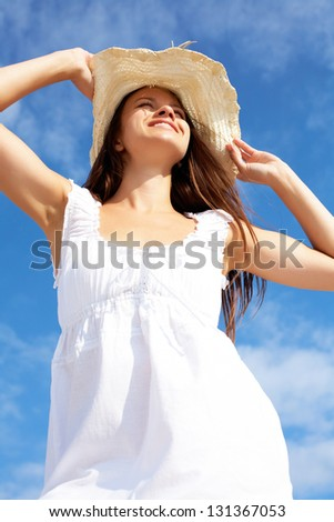 Portrait of pretty young lady in white dress and hat against blue sky - stock photo