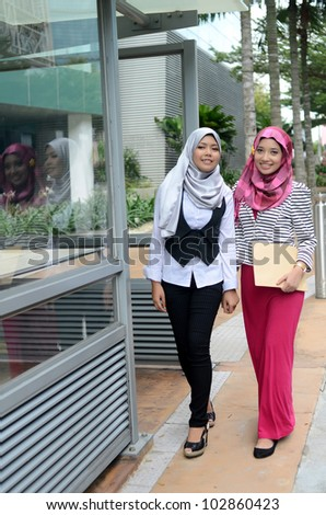 Portrait of pretty young Muslim woman walk together while hold file - stock photo