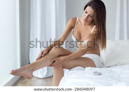 Portrait of pretty young woman applying body cream on legs. - stock photo