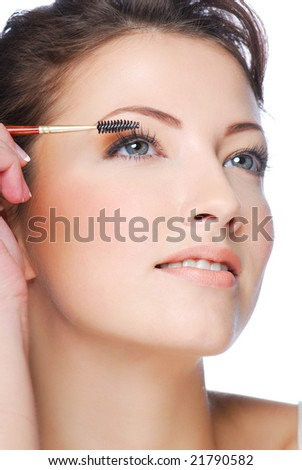 Portrait of pretty young  woman applying mascara using lash brush - stock photo