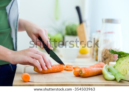 Portrait of pretty young woman cutting vegetables in the kitchen. - stock photo