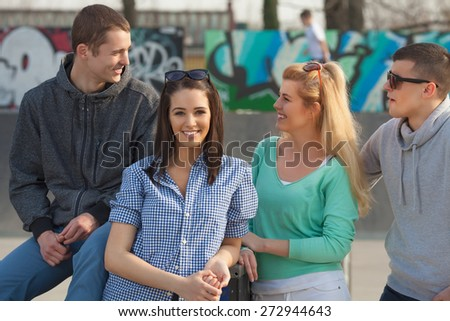 Portrait of pretty young woman hanging out with her friends in a skate park or schooolyard - stock photo