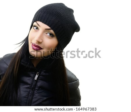 portrait of pretty young woman in black hat and jacket, studio shot over white - stock photo