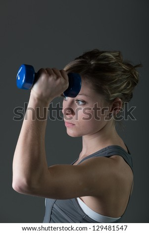 Portrait of pretty, young woman lifting dumbbells during workout - stock photo