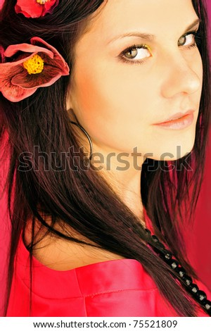 Portrait of pretty young woman on pink background with flower in her hair - stock photo