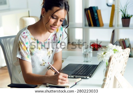 Portrait of pretty young woman using her laptop in the office. - stock photo