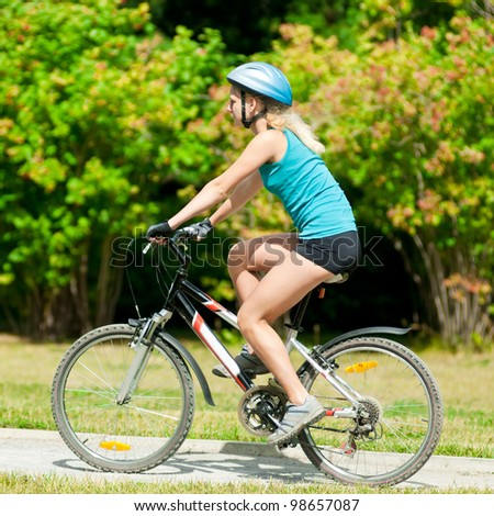 Portrait of pretty young woman with bicycle in a park - outdoor - stock photo
