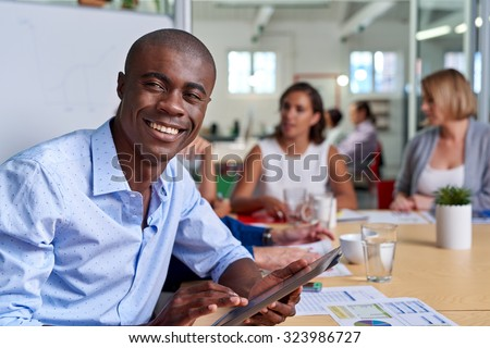 portrait of professional african black business man during coworkers boardroom meeting with tablet computer taking notes - stock photo