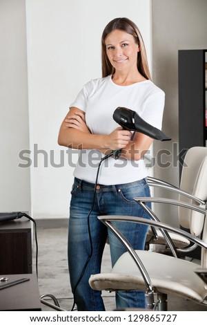 Portrait of professional female hairdresser holding hair dryer at salon - stock photo