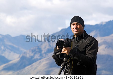 Portrait of professional on location and nature photographer (man) during work outdoor. - stock photo