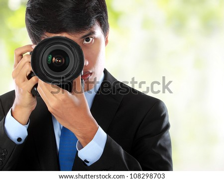 portrait of professional photographer with camera aiming - stock photo