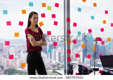 Portrait of proud assistant with arms crossed.The woman stands in office at high floor, against window full of adhesive notes with tasks - stock photo