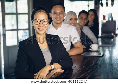 portrait of proud businesswoman standing in front of her team - stock photo