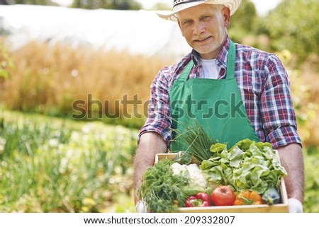 Portrait of proud man with his harvest in home garden  - stock photo