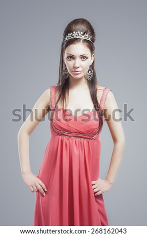 Portrait of Provocative Sexy Caucasian Brunette female with Tiara Crown wearing Peachy Pink Fashionable Dress. Against Grey Background. Vertical Image Composition - stock photo