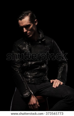 portrait of punk model in leather jacket posing seated in dark studio background - stock photo
