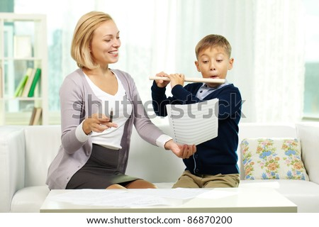 Portrait of pupil playing the flute while looking at notes in tutor?s hand - stock photo