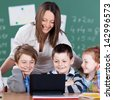 Portrait of pupils and teacher looking at digital tablet in the classroom - stock photo