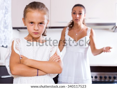 Portrait of quarrelling young woman and female child indoors - stock photo