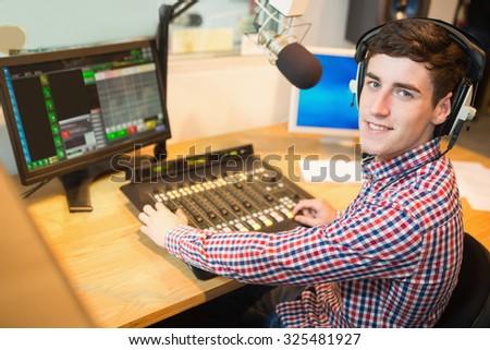 Portrait of radio host operating sound mixer on table at studio - stock photo