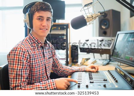 Portrait of radio host using sound mixer on table in studio - stock photo