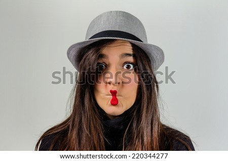 Portrait of real young girl gesturing with her red lips over a gray background - stock photo