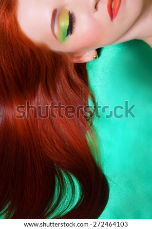 Portrait of red-haired girl with bright makeup on a green background - stock photo