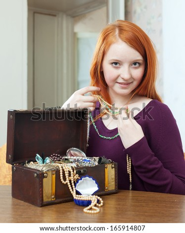 portrait of  red-headed  girl tries necklace in home interior - stock photo