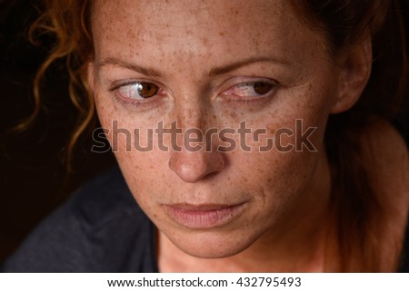 Portrait of redhead woman anxiety expression with tears in eyes trying not to cry suppressed emotion looking back  - stock photo