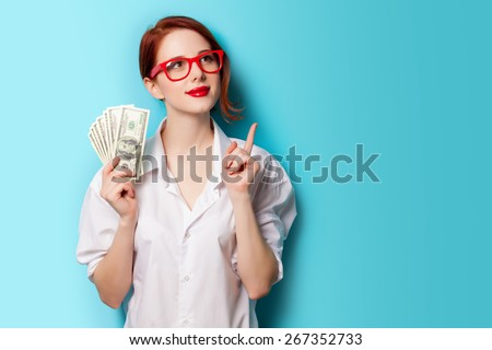 Portrait of redhead women in red glasses with money on blue background - stock photo