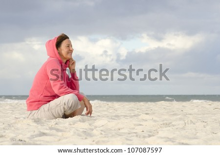Portrait of relaxed attractive looking mature woman in pink sweater, sitting daydreaming and contemplating at beach, isolated with storm clouds and ocean as background and copy space. - stock photo