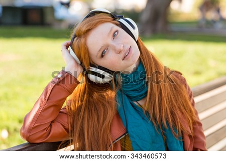 Portrait of relaxed charming young lady with beautiful long red hair enjoying music in headphones on bench in park - stock photo