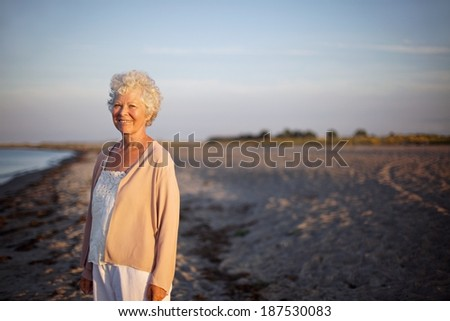 Portrait of relaxed elderly woman standing at the beach. Happy old lady standing alone on the beach with lots of copyspace. Relaxed senior caucasian woman outdoors smiling at camera - stock photo