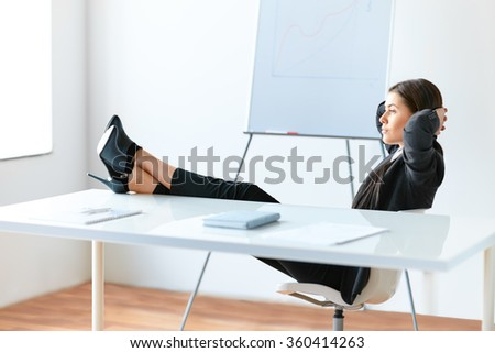 Portrait of relaxed pretty business woman sitting with legs on desk in the office - stock photo