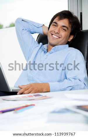 Portrait of relaxed young male interior designer with laptop sitting in office chair - stock photo