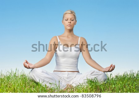 Portrait of relaxed young woman meditating outdoors. - stock photo