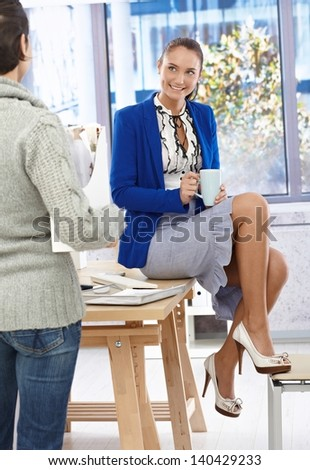 Portrait of relaxing pretty businesswoman in fancy skirt and high heels sitting on desk in office chatting to colleague while on coffee break. - stock photo
