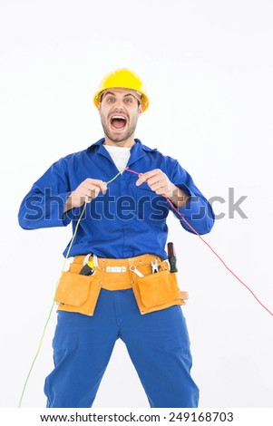 Portrait of repairman screaming while holding wires against white background - stock photo