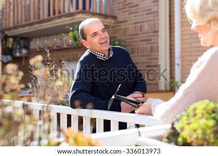Portrait of retired couple on a terrace: old husband is holding a cup of hot beverage and talking to his wife who is holding gardening tools - stock photo