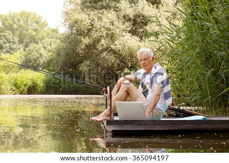 Portrait of retired man fishing at lakeshore and surfing on internet while sitting on the pier. - stock photo