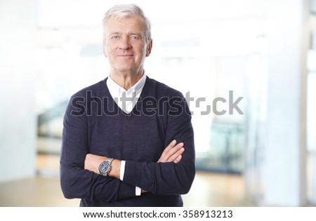 Portrait of retired professional man standing with arms crossed at office and looking at camera. - stock photo