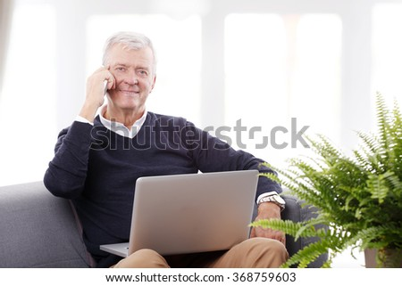 Portrait of retired senior man sitting at home and working online with laptop while making call.  - stock photo