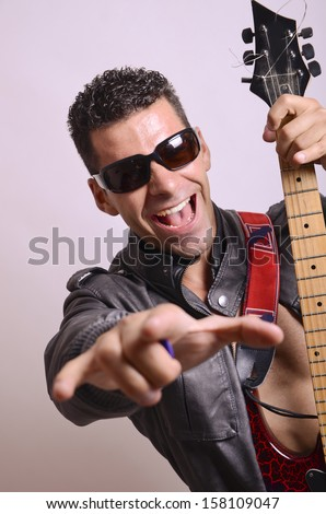 Portrait of rockstar with guitar looking at the view - stock photo