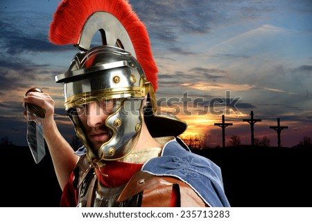 Portrait of Roman soldier brandishing sword with Calvary and crosses at sunset - stock photo